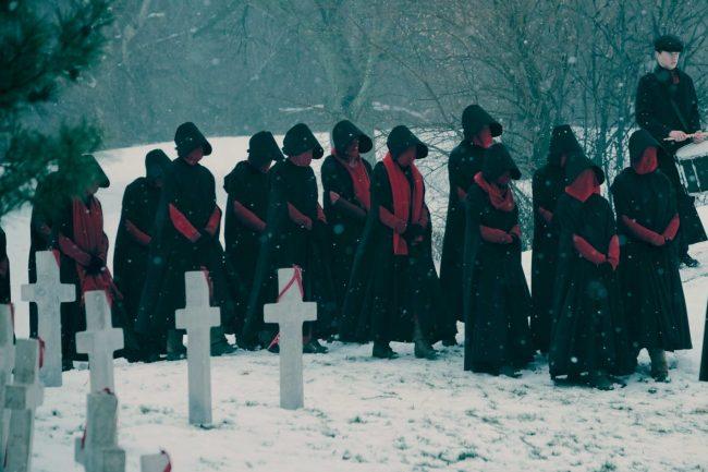 The Handmaid's Tale Sesong 2 ser også ut til å forsette sin imponerende innsats på det visuelle, som bildene nedenfor viser. Det ser ut som en begravelse, med tjenestepikene kledd i svarte kapper med røde masker som dekker ansiktene deres.
